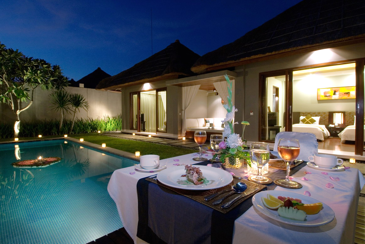 Fancy dinner by a backyard swimming pool surround by led lights