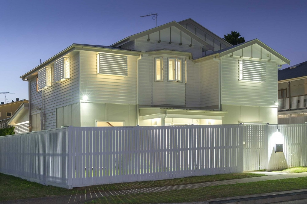 Well lit two story home with white picket fence