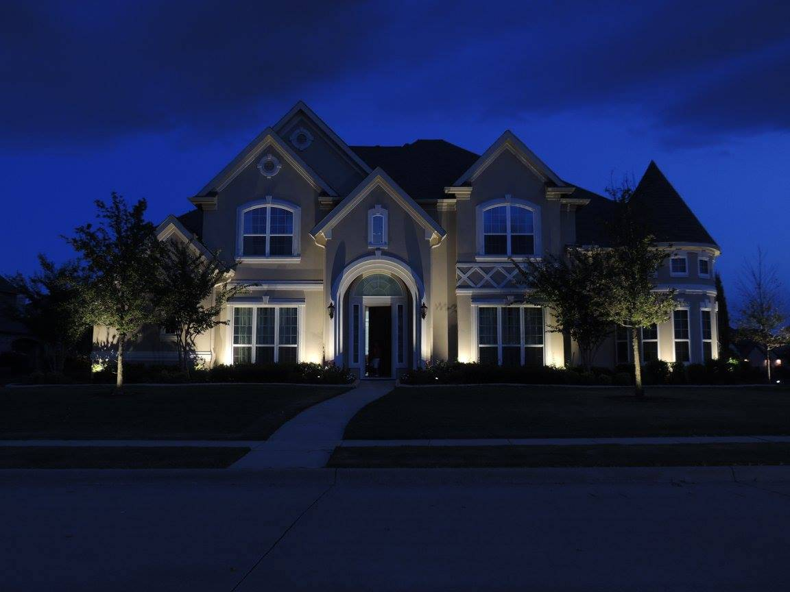 A suburban home at dusk is illuminated by exterior lighting
