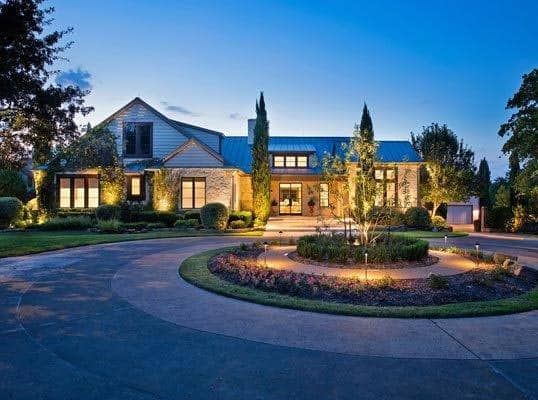 a beautiful well-lit home and circular driveway with landscaping