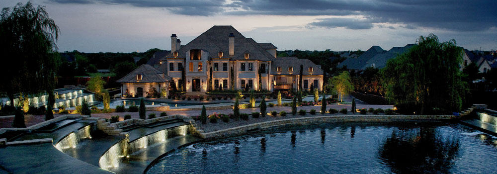 Waterside mansion lit up at night with beautiful landscaping