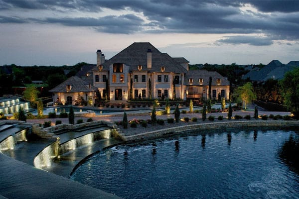 A waterside mansion is lit up at night with beautiful landscaping
