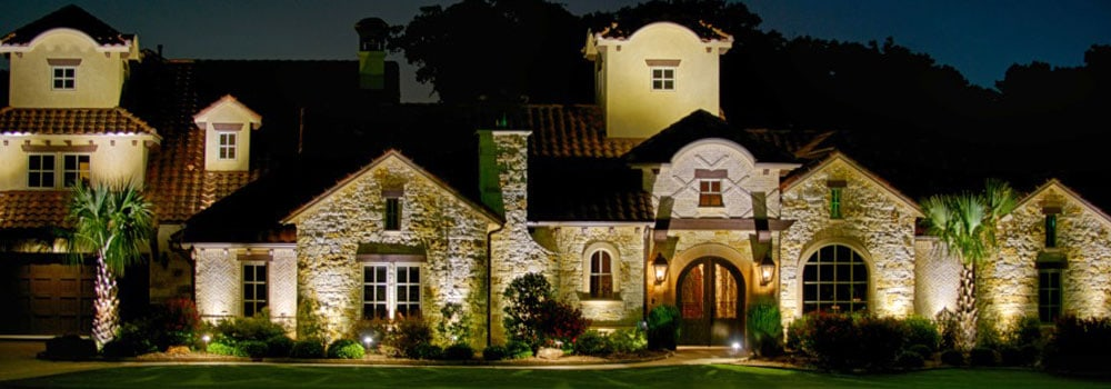 Two story Spanish style home at night
