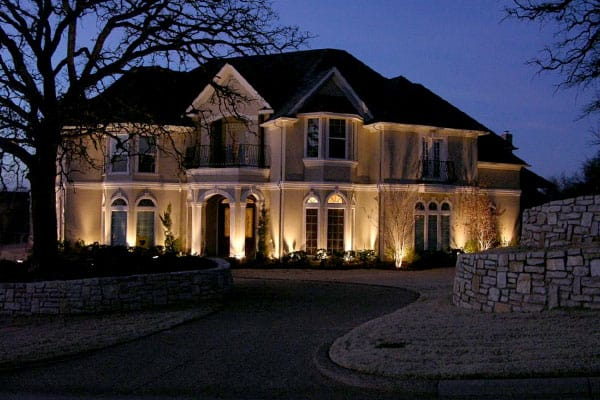 Two-story home lit up with security lighting at night
