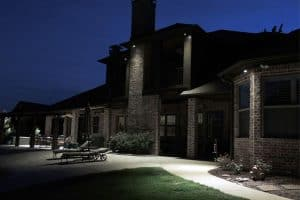 Backyard security lighting overlooking poolside patio furniture