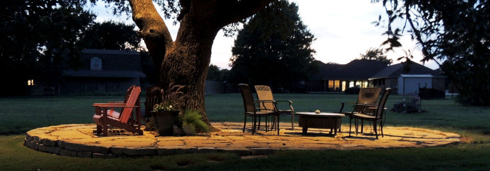 LED Lighting on a tree and patio furniture on stone slab in the backyard