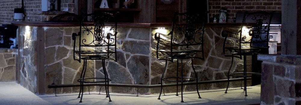 Iron patio barstools in backyard light up at night