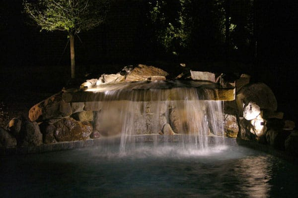 A Stone waterfall grotto in a backyard pool illuminated by lighting
