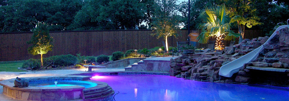 Nice pool with stone feature and slide at night