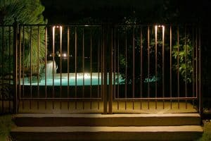 Light shining on a waterfall flowing into a pool can be seen through a fence