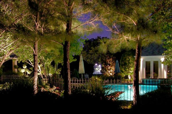 A Pool can be seen through a fence lit up at night