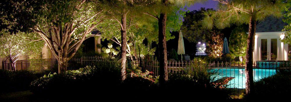 Iron fence surrounding pool with LED security lighting at night