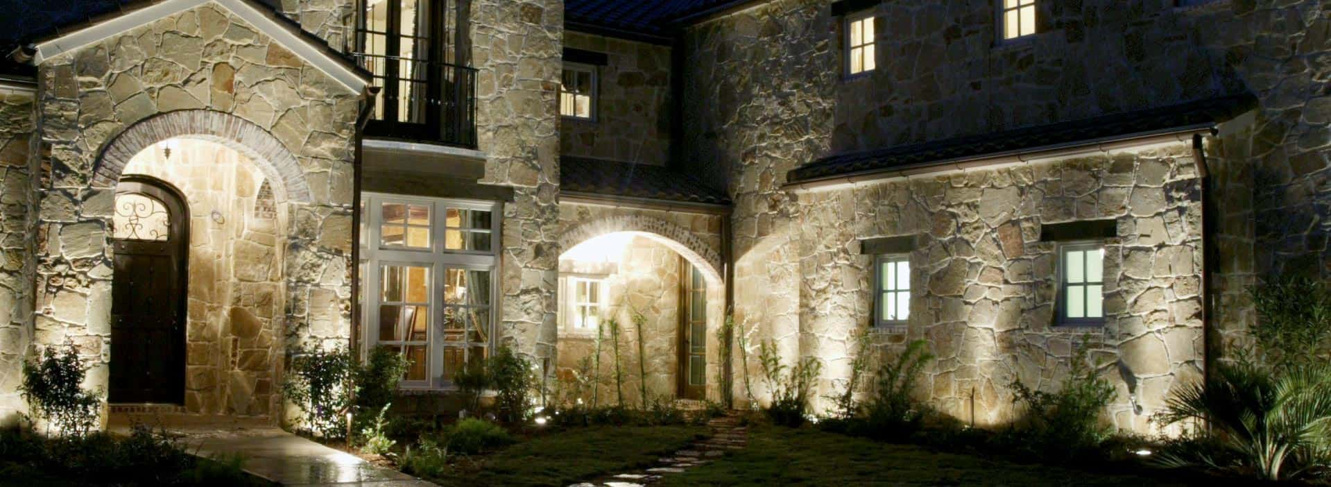 A home's beautiful stonework is accented by outdoor lighting