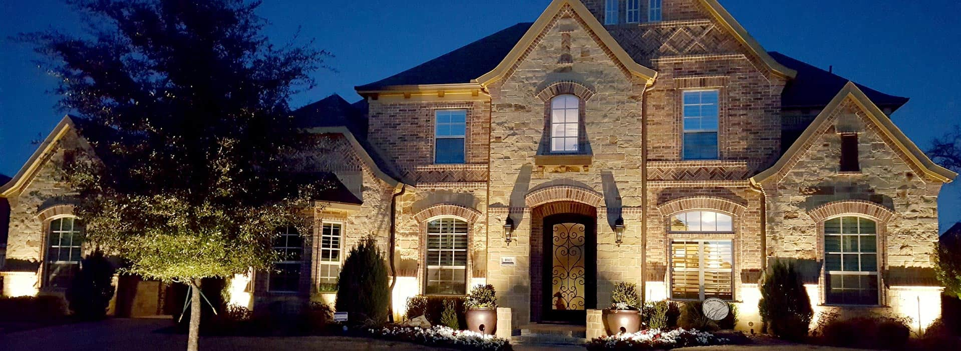 Bright lights shine up at the outdoor face of a beautiful Dallas home